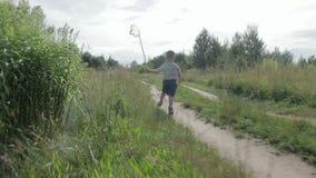 Um rapaz pequeno alegre corre com uma rede para uma borboleta filme