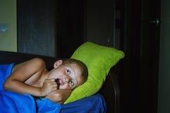 Um rapaz pequeno assustado receoso na cama na noite, infância teme foto de stock