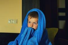 Um rapaz pequeno assustado receoso na cama na noite, infância teme foto de stock royalty free