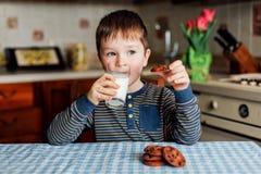 Um rapaz pequeno bebe o leite e come cookies na cozinha na manhã imagem de stock
