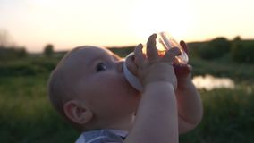 Um rapaz pequeno bebe uma bebida de uma garrafa de bebê no campo no movimento lento filme