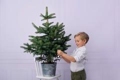 Um rapaz pequeno bonito, cabelo louro, veste uma árvore de Natal com bolhas de prata imagem de stock royalty free