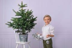 Um rapaz pequeno bonito, cabelo louro, veste uma árvore de Natal com bolhas de prata fotos de stock royalty free