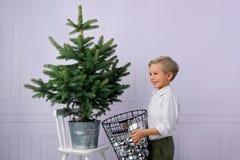 Um rapaz pequeno bonito, cabelo louro, veste uma árvore de Natal com bolhas de prata imagens de stock royalty free