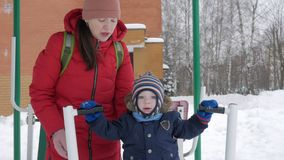 Um rapaz pequeno bonito e uma mãe nova são contratados no equipamento exterior do exercício Ele ` s duramente para que uma crianç filme