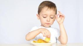 Um rapaz pequeno bonito está sentando-se na tabela e está comendo-se microplaquetas Não uma dieta saudável para crianças vídeos de arquivo