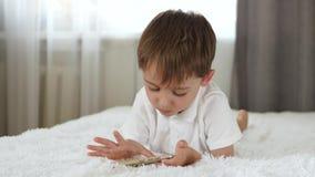Um rapaz pequeno bonito olha na tela do smartphone ao encontrar-se na cama As brincadeiras no smartphone video estoque