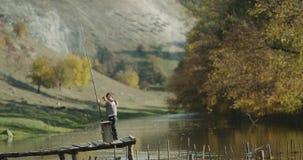 Um rapaz pequeno bonito que guarda uma vara de pesca grande em uma ponte ao lado do lago e do jogo vídeos de arquivo