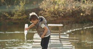 Um rapaz pequeno bonito que joga com uma garrafa no lago, estando na parte superior da ponte 4K filme