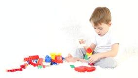 Um rapaz pequeno bonito senta-se e joga-se com blocos do construtor da cor A criança constrói uma casa do desenhista E vídeos de arquivo