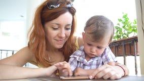Um rapaz pequeno com mamã usa o Internet no smartphone vídeos de arquivo