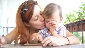 Um rapaz pequeno com mamã usa o Internet no smartphone filme