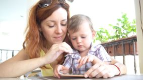 Um rapaz pequeno com mamã usa o Internet no smartphone video estoque
