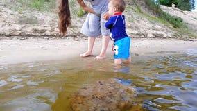 Um rapaz pequeno com seus jogos da mãe na água perto da costa arenosa vídeos de arquivo