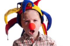 Um rapaz pequeno com um palhaço do nariz do palhaço em um chapéu Imagem de Stock