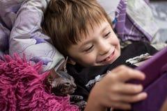 Um rapaz pequeno com uma mentira calva da esfinge do gato na cama sob uma cobertura vermelha e olhar na tabuleta imagem de stock royalty free