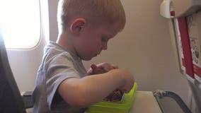 Um rapaz pequeno come a massa com carne no plano durante o voo video estoque