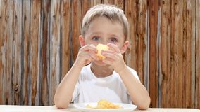 Um rapaz pequeno come microplaquetas com prazer Crianças comendo não saudáveis Alimento insalubre video estoque