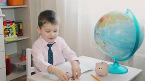 Um rapaz pequeno conta suas economias em uma calculadora e escreve-as em um caderno HD filme