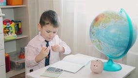 Um rapaz pequeno conta suas economias em uma calculadora e escreve-as em um caderno filme