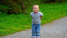 Um rapaz pequeno corre através do parque video estoque