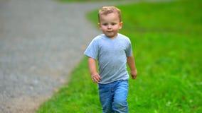 Um rapaz pequeno corre através do parque filme