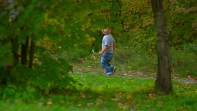 Um rapaz pequeno corre através do parque, escondendo a árvore do ha video estoque