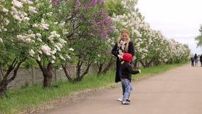 Um rapaz pequeno corre em torno de seu parque da mãe na primavera entre as árvores de florescência video estoque