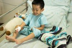 Um rapaz pequeno doente na cama de hospital imagens de stock