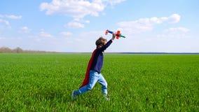 Um rapaz pequeno em um casaco e em uma máscara vermelhos guarda um avião em sua mão e imagina-o voar filme