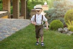 Um rapaz pequeno em um chapéu de palha anda no parque imagem de stock