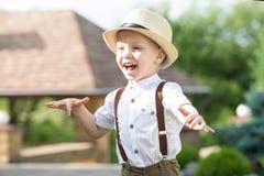 Um rapaz pequeno em um chapéu de palha anda no parque fotografia de stock