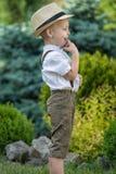 Um rapaz pequeno em um chapéu de palha anda no parque Menino pequeno, tímido fotos de stock