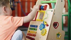 Um rapaz pequeno em um jardim de infância joga um brinquedo tornando-se vídeos de arquivo