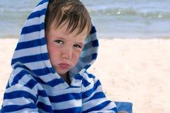 Um rapaz pequeno em um roupão listrado no litoral com dermatite atópica foi ofendido e amuou seus bordos, Imagem de Stock Royalty Free