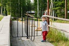 Um rapaz pequeno em uma camisa e em um chapéu está perto do torniquete no verão foto de stock royalty free