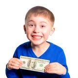 Um rapaz pequeno em uma camiseta azul sorri e guarda cem dólares imagem de stock royalty free