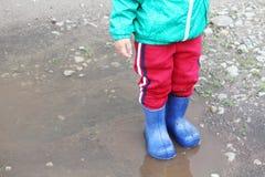 Um rapaz pequeno em uma po?a nas botas de borracha fotografia de stock