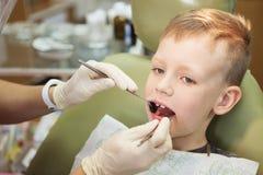 Um rapaz pequeno em uma recepção do ` s do dentista em uma clínica dental Childr foto de stock