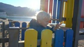 Um rapaz pequeno escala acima a corrediça na maneira que observa uma gota da água cintilar no sol e querer saber nele filme