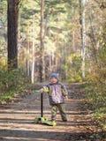 Um rapaz pequeno está com um 'trotinette' no parque fotografia de stock