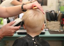 Um rapaz pequeno está cortando um cabeleireiro no salão de beleza A criança está olhando uns desenhos animados Tela verde em um p foto de stock royalty free
