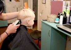 Um rapaz pequeno está cortando um cabeleireiro no salão de beleza A criança está olhando uns desenhos animados Tela verde em um p imagens de stock royalty free