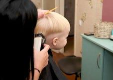 Um rapaz pequeno está cortando um cabeleireiro no salão de beleza A criança está olhando uns desenhos animados Tela verde em um p fotos de stock