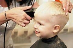Um rapaz pequeno está cortando um cabeleireiro no salão de beleza A criança está olhando uns desenhos animados Tela verde em um p imagens de stock