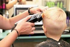 Um rapaz pequeno está cortando um cabeleireiro no salão de beleza A criança está olhando uns desenhos animados Tela verde em um p foto de stock