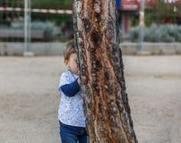 Um rapaz pequeno está escondendo atrás de uma árvore Foto de Stock Royalty Free