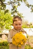 Um rapaz pequeno está guardando um grande ramalhete dos dentes-de-leão amarelos, tímido, fazendo caretas, um presente a sua mãe fotografia de stock