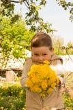 Um rapaz pequeno está guardando um grande ramalhete dos dentes-de-leão amarelos, tímido, fazendo caretas, um presente a sua mãe foto de stock royalty free