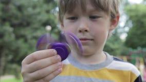 Um rapaz pequeno está jogando com um girador O menino está girando um girador em sua mão filme